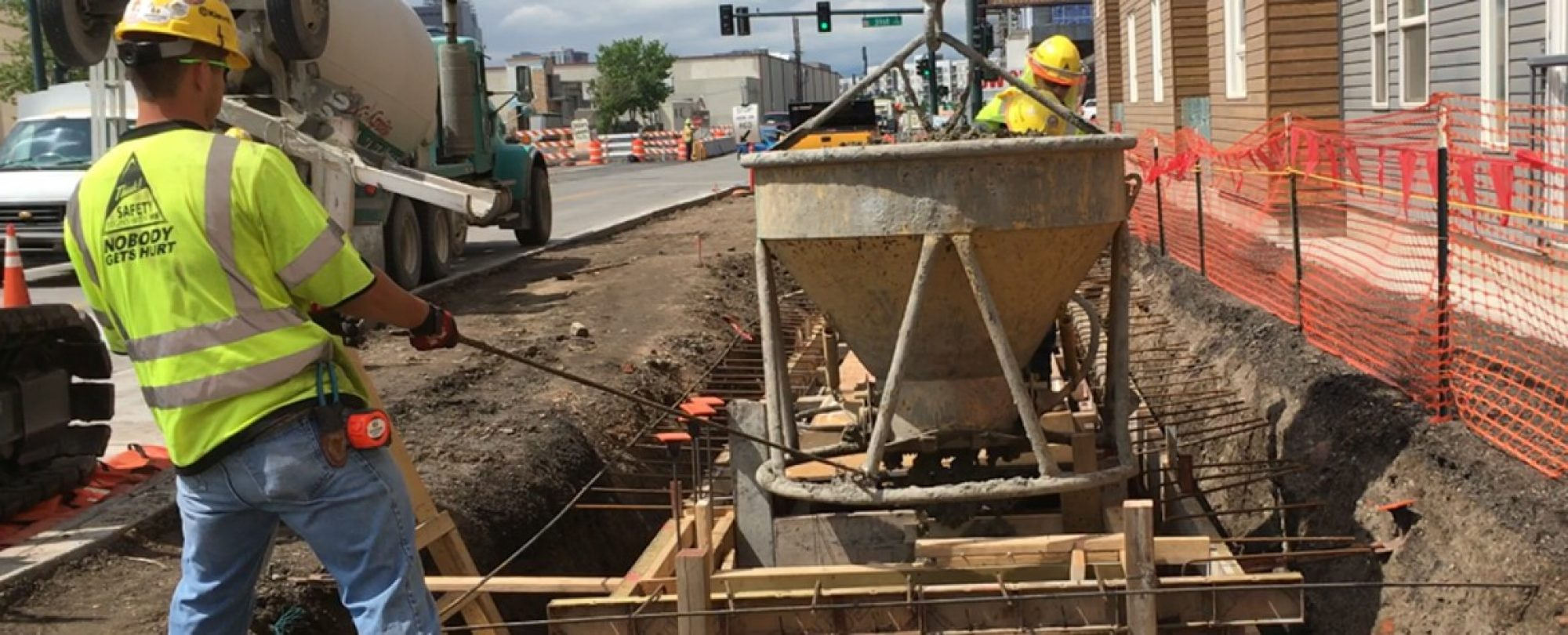 crew pouring concrete for stormwater planter next to roadway