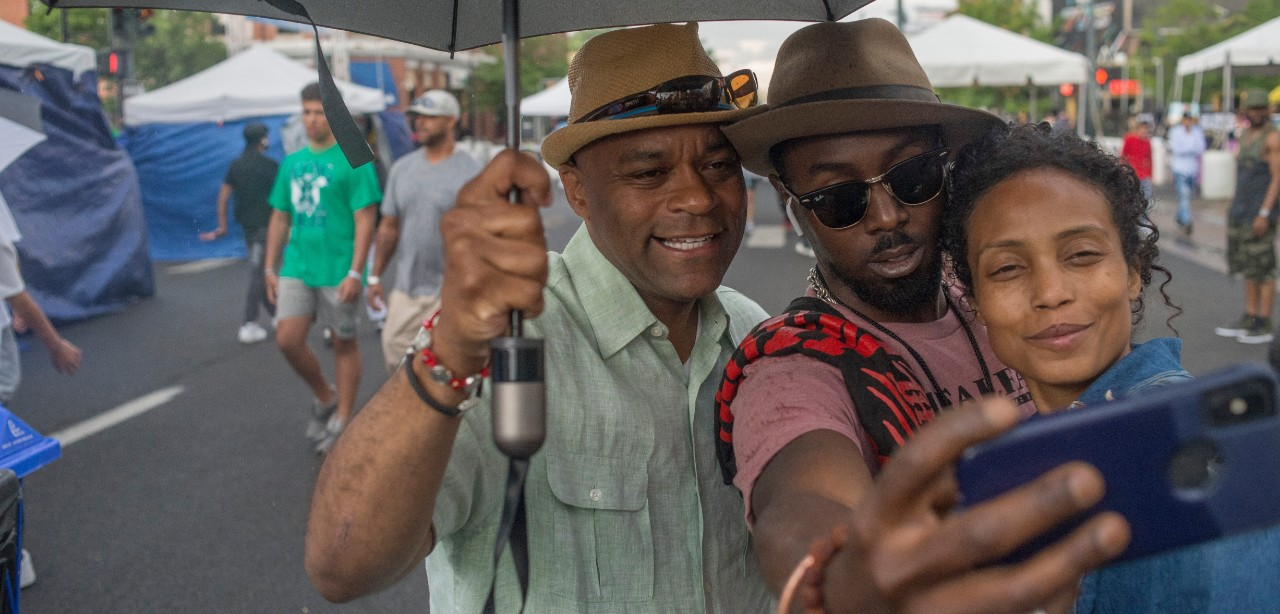 Mayor Hancock taking a selfie photo with two attendees at Juneteenth