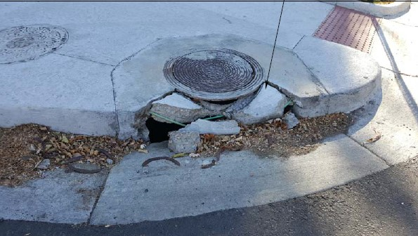 damaged curb around utility cover and manhole next to ADA ramp