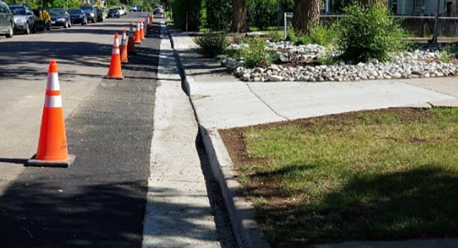 orange traffic cones next to completed curb and gutter repairs with new concrete and asphalt