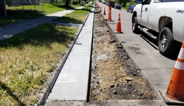 fresh concrete poured to create curb and gutter, with tree lawn on one side and unfinished roadway on the other