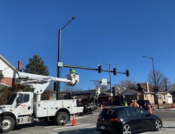 Crews installing mast arm for new signal on Lincoln at Exposition