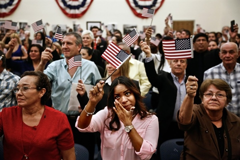 New U.S. Citizens waving flags, smiling, and in tears as they celebrate at the end of the citizenship ceremony