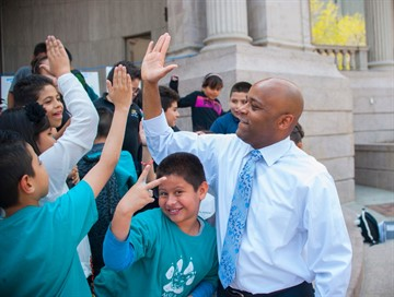 Mayor high fiving kids