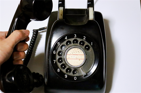 A hand holding the receiver of a black rotary phone