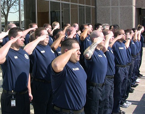 Photo of sheriff academy recruits saluting taken at an angle