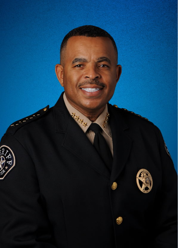 Sheriff Elias Diggins wearing his uniform facing the camera and smiling
